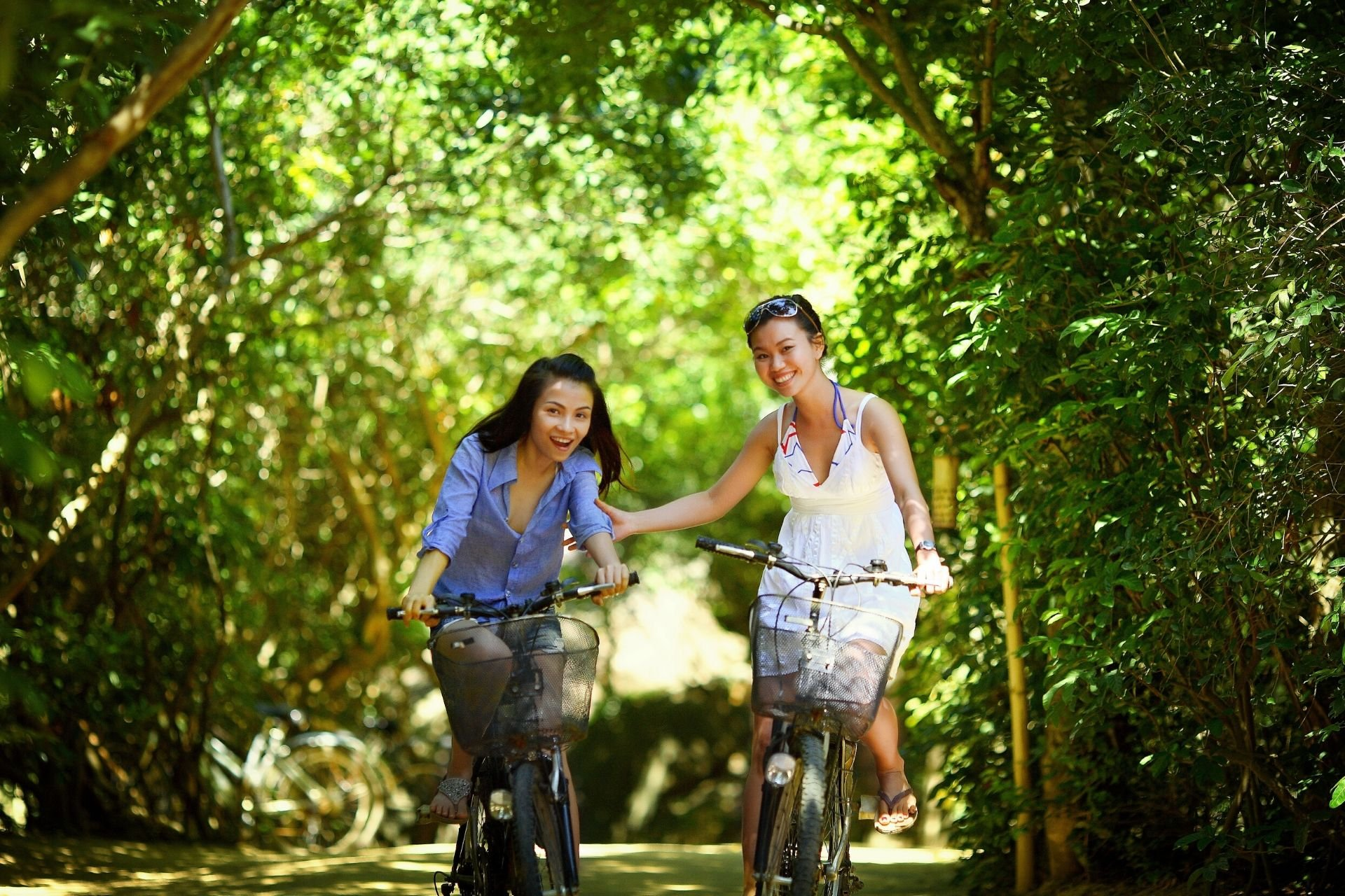 two women riding bikes surrounded by nature
