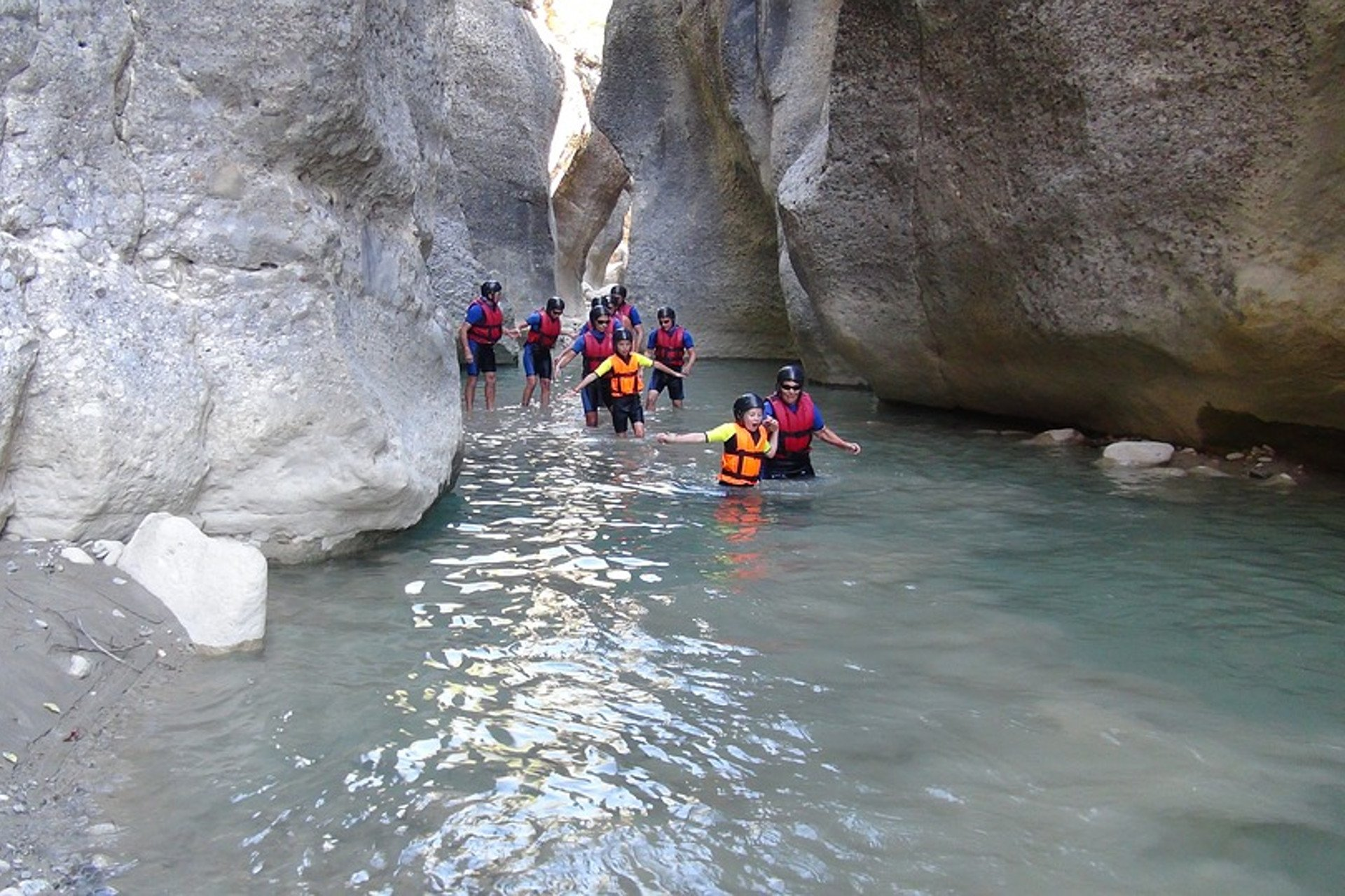 a group of canyonists walking down a river