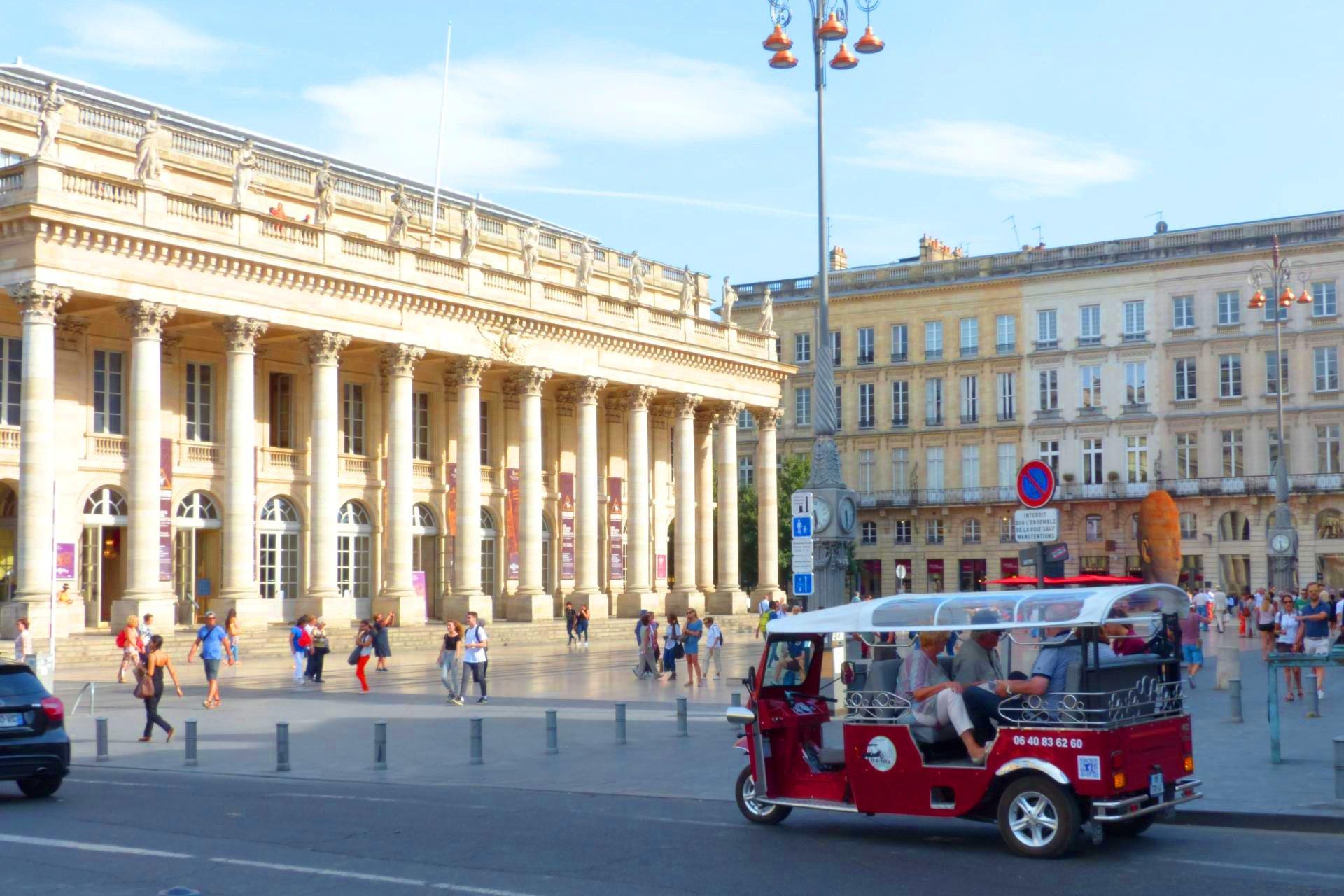 Un tuk tuk électrique devant l'opéra de Bordeaux