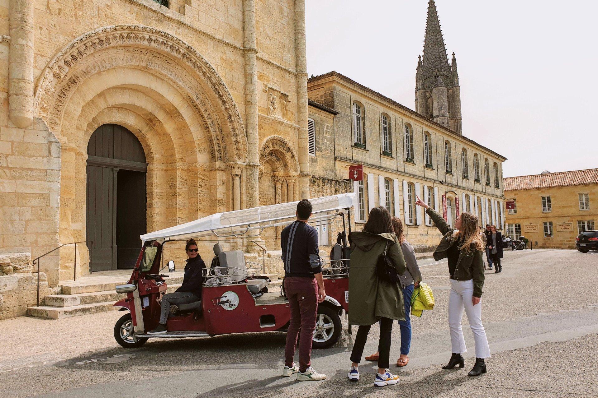 Le tuk-tuk électrique et ses passagers devant un bâtiment historique de Saint Emilion