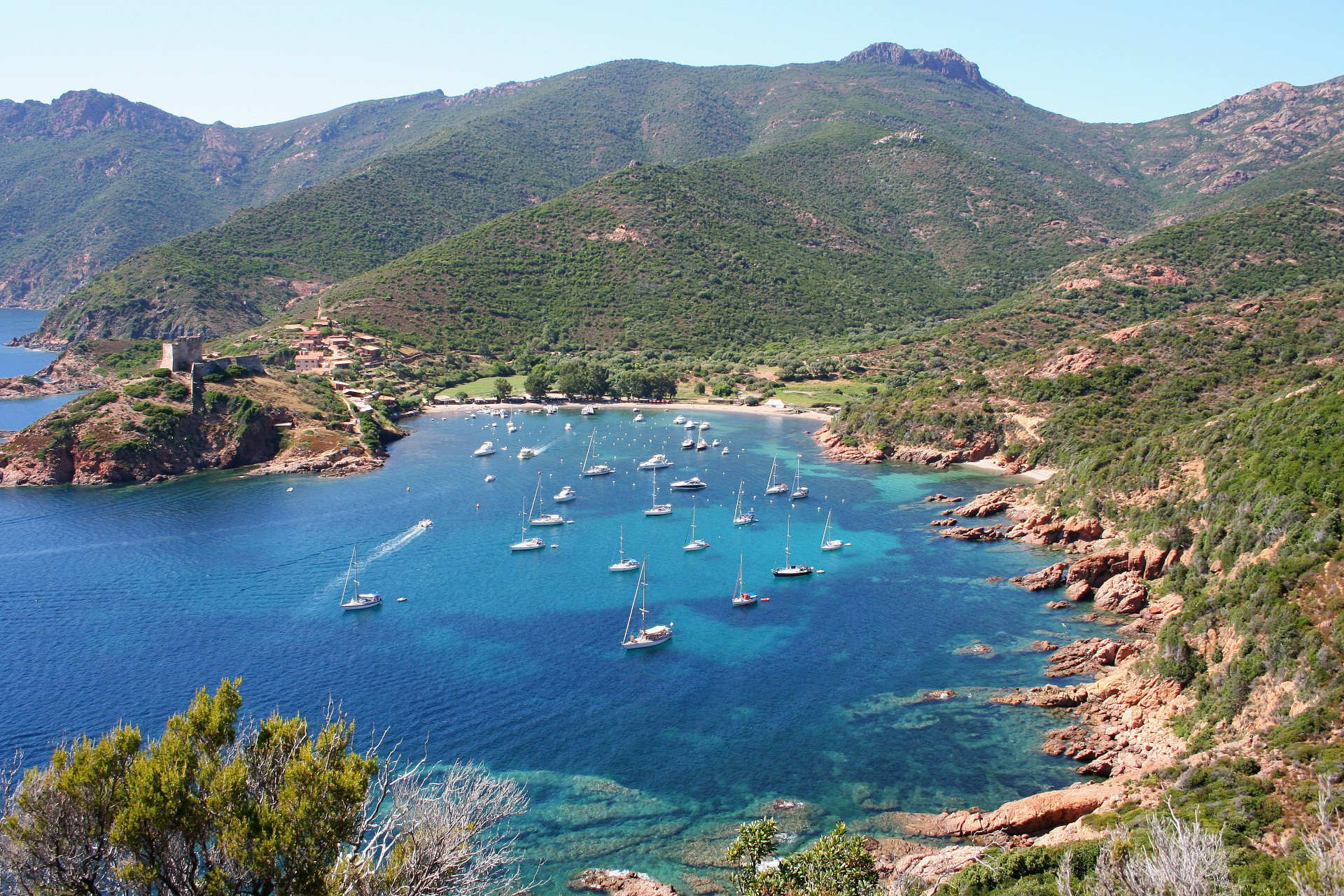 Sailing boats sheltering in a clear water creek along the Corsican coast