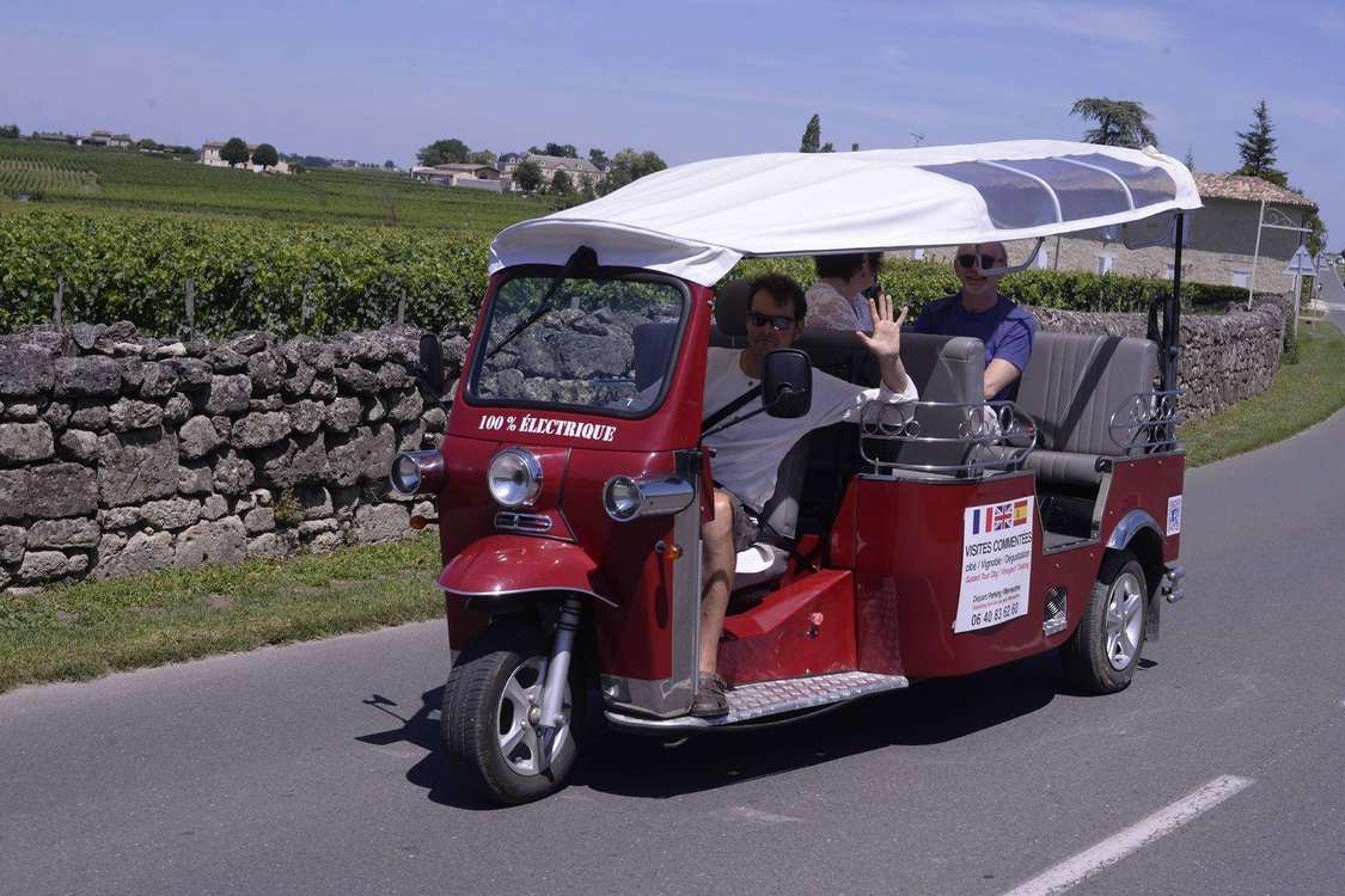 Le tuk-tuk électrique et ses passagers sur une route le long des vignobles