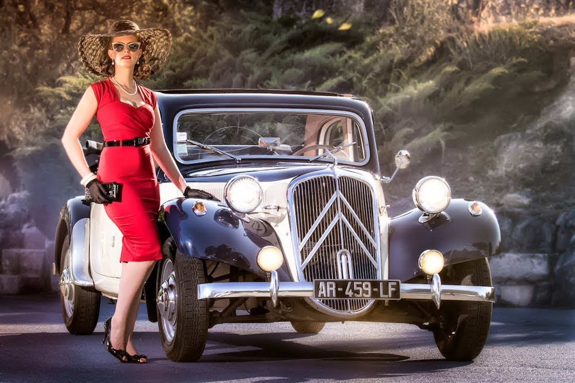 An elegant woman red dress standing by a Citroën vintage car