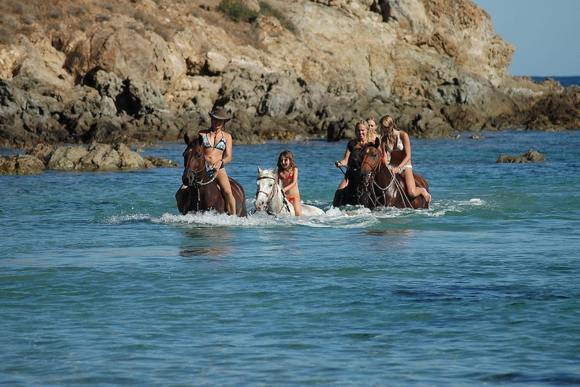 Five horses with their riders strolling in shallow water along the Corsican coast