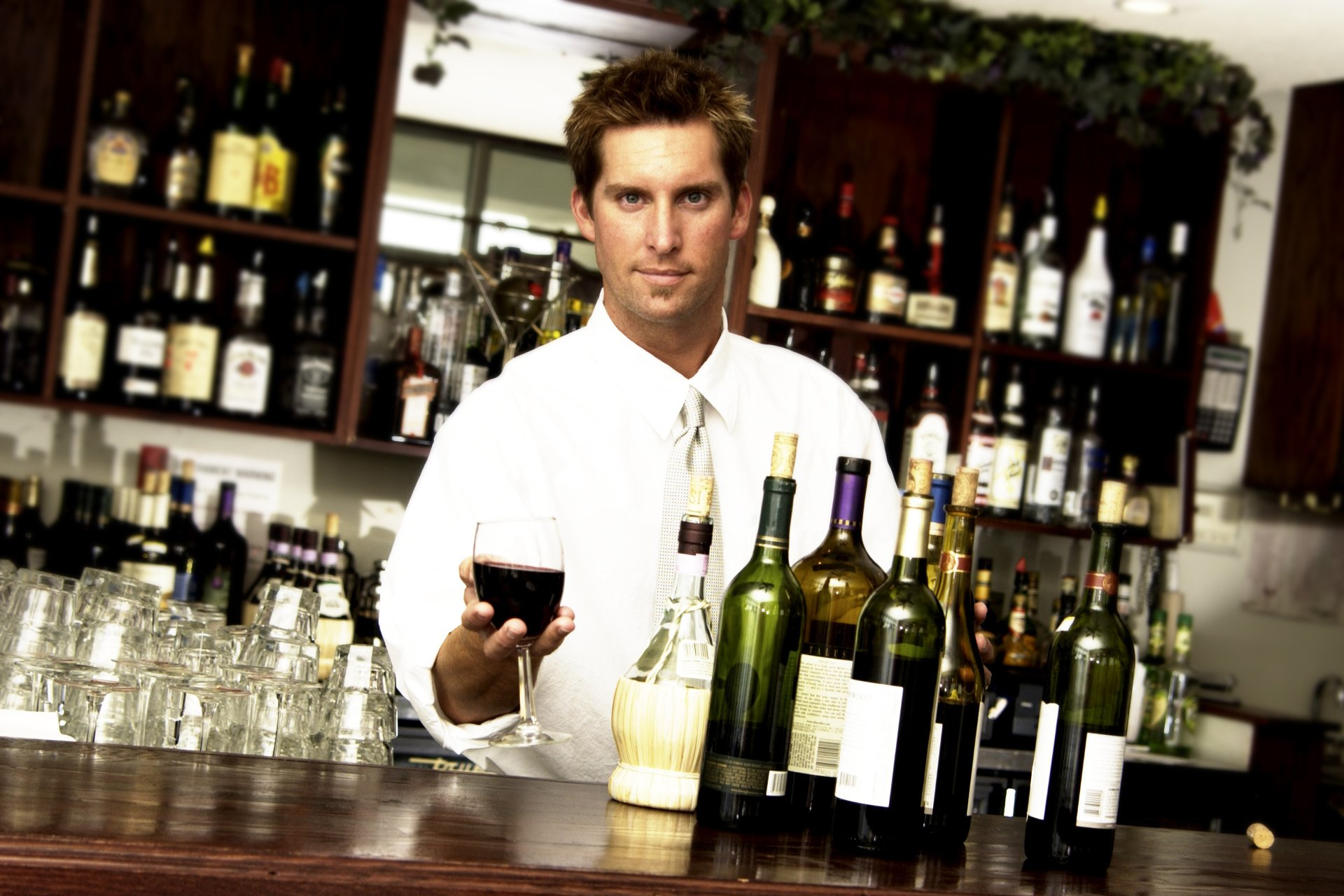A sommelier at his counter offering a glass of wine
