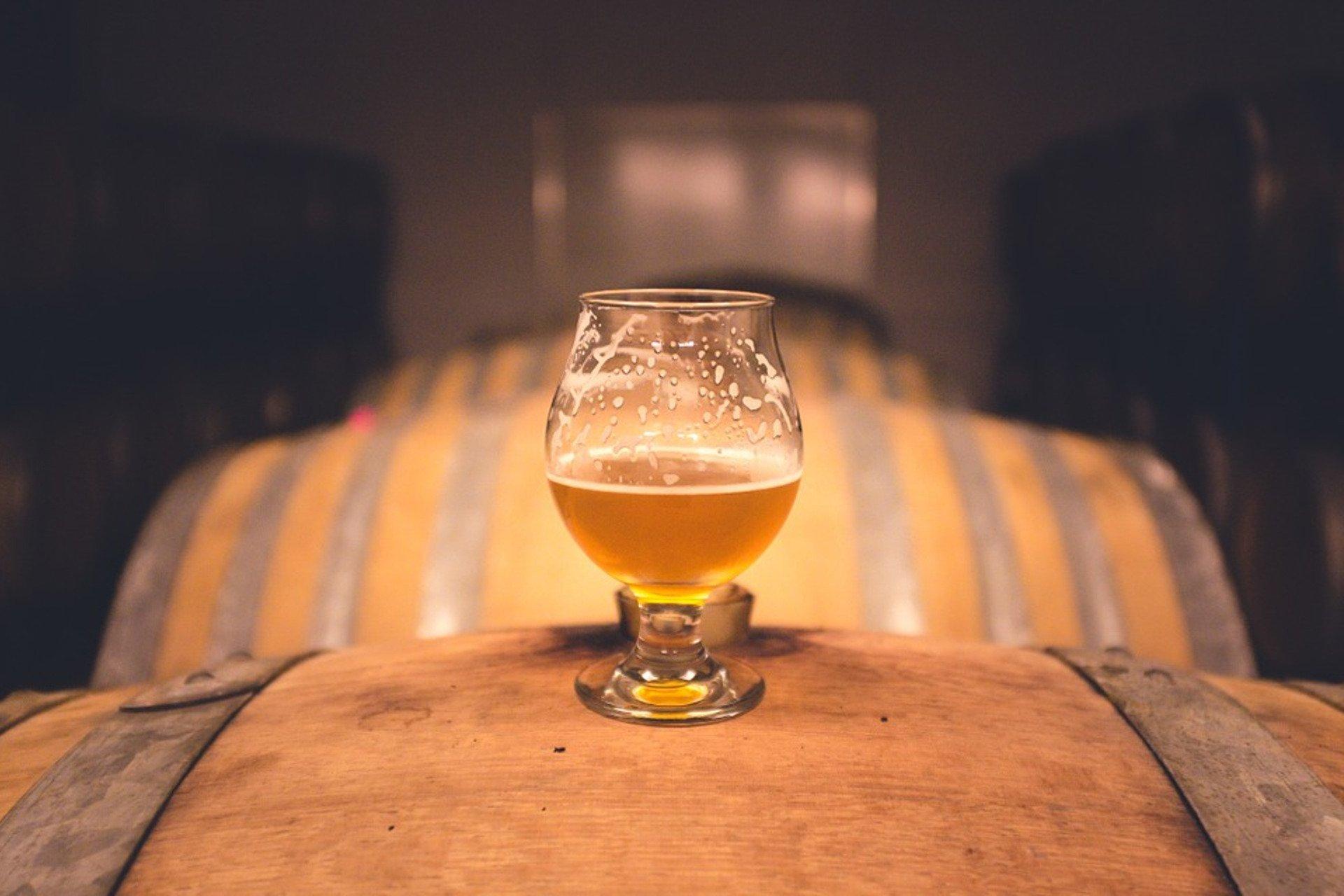 un fut en bois et un verre de biere blonde
