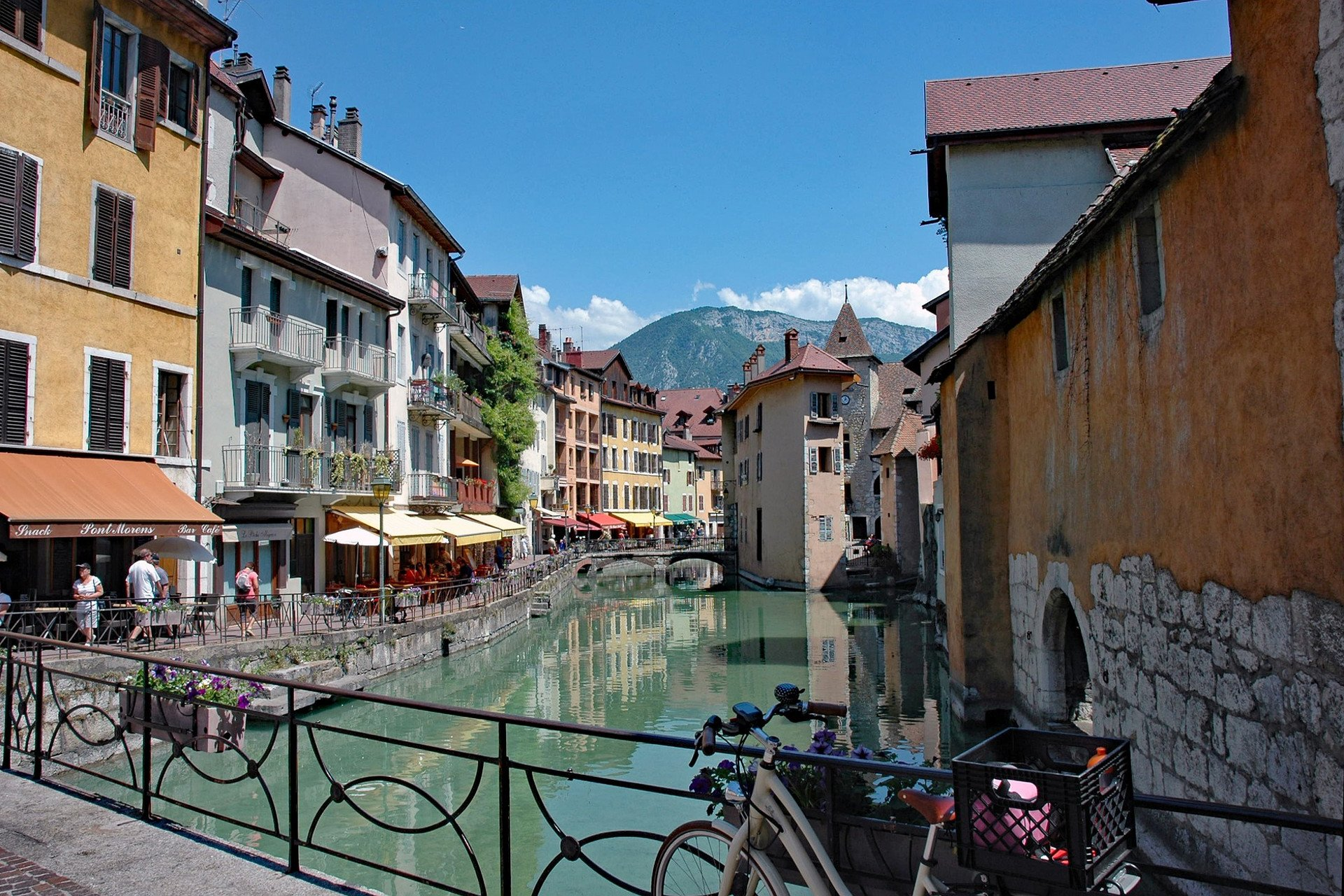 Canal du Thiou in Annecy old town center with mountain background