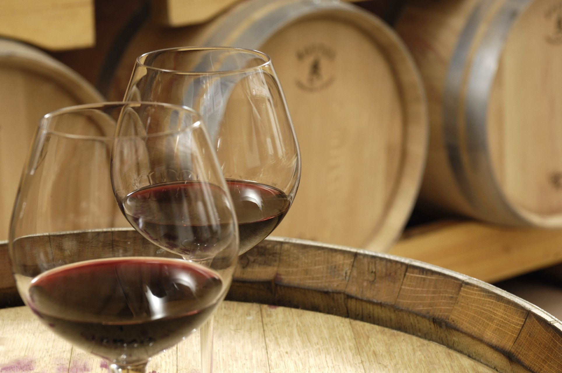 two red wine glasses with wooden barrels