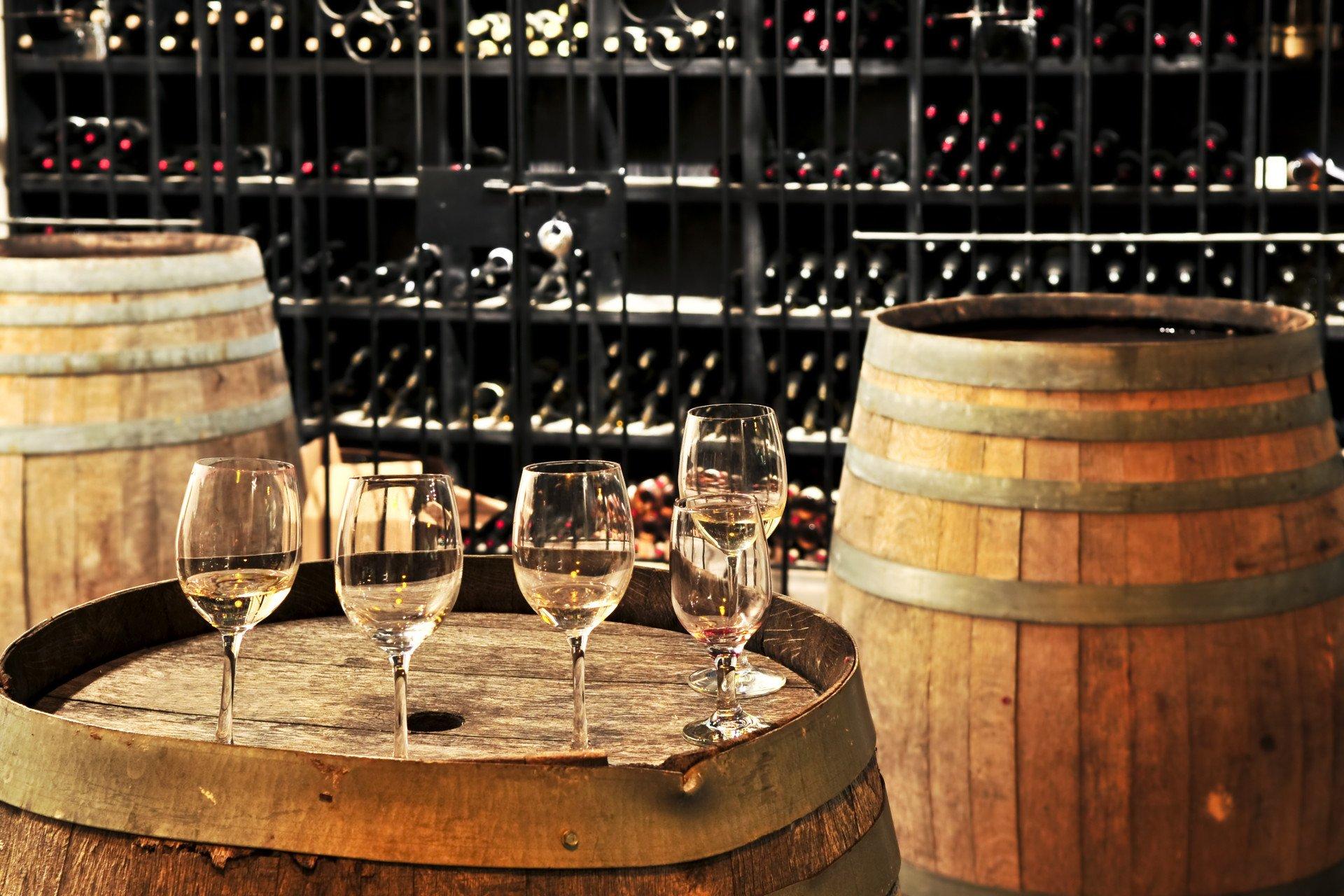 Des verres posés sur un tonneau pendant une dégustation de vin